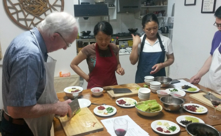 Brendan Halligan, on a visit to China, 2014, participate in a lesson in Chinese cookery.